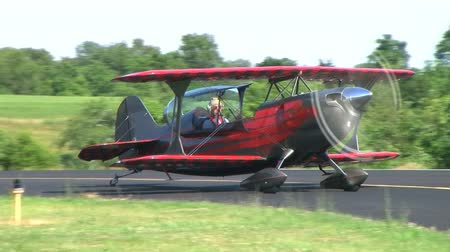 letadlo : Christen Eagle II biplane taxis on runway at small airport and releases smoke.