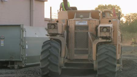 pulverizado : Heavy equipment working slowly crushing pavement on construction site.