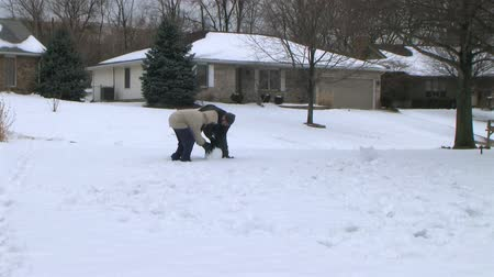 lití : Time lapse of couple working together and having fun building a snowman.