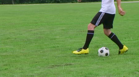jogador : Young soccer player demonstrates footwork by dribbling ball, dolly shot.