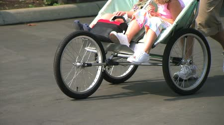 toló : Closeup of legs and feet as mother gets exercise by pushing children in three wheel stroller in park.  Stock mozgókép