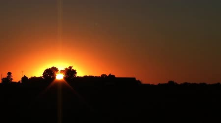 natura : Time lapse of sunset behind silhouette of house on rural midwest farm.