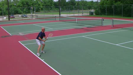 tennis game : Tennis player volleys using forehand technique while playing on public court, crane shot.