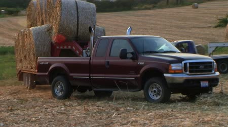 trucks : Pickup trucks haul round hay bale load out of hayfield on trailer during harvest, with external audio.