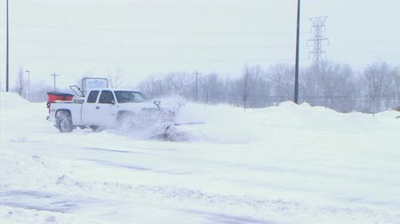 arado : Truck works to clear parking lot during late winter snowstorm in March. Stock Footage