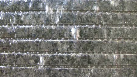 gray background : Water wall with beads forming and creating pattern in crevices of granite, with external audio.