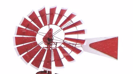 Close-up of red and white windmill spinning during late winter snowstorm.