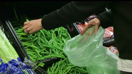 овощи : Woman selecting fresh green beans in grocery store produce department.