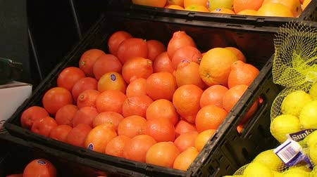 фрукты : West Chester - MARCH 21: Female shopper (name withheld) from Monroe, OH chooses fresh oranges at local market March 21, 2007 in West Chester, OH.