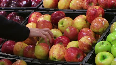 jabłka : Woman selecting fresh red apples in grocery store produce department.