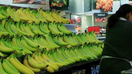 Employee stocking large banana display while working in produce department of supermarket. Dostupné videozáznamy