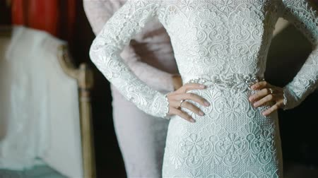 helping : Bride touches her lace wedding dress with her beautiful manicured fingers