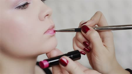 искушение : Professional make-up: pink lipstick application. Close-up
