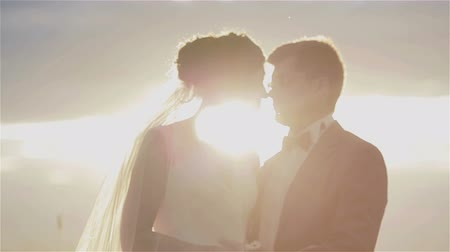evli : Loving married couple kissing in sunlight silhouetted