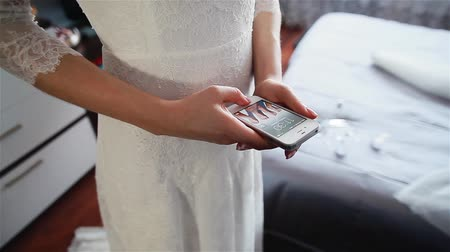 uzun : Close-up of hands of a young bride checking her phone