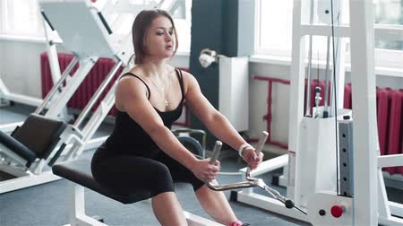 evezés : Young woman training in gym on rowing machine. Middle shot Stock mozgókép