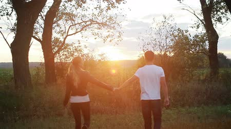 hour hand : Young couple in love holding hands walking in field at sunset. Slow motion