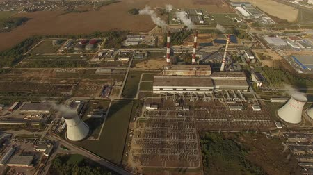 producing energy : 4K aerial shot flight over power plant with smoking pipes industrial view