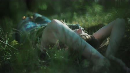 tizenéves lányok : Young woman in the forest lying on the moss and touching the plants around her. Close up