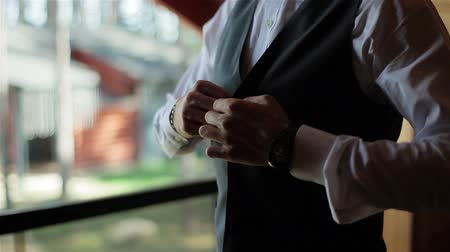 гангстер : Stylish man in a suit and white shirt buttoning a vest waistcoat standing near the window. Close up