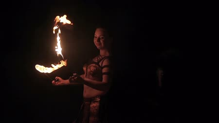 bohyně : Fire show performance. Female fire performer woman dancing with burning fire torches on a black background. Close-up. Slow motion