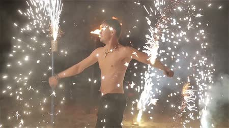 fogo de artifício : Fire show performance. Male fire performer dance twirling sparkling fireworks batons staff. Slow motion