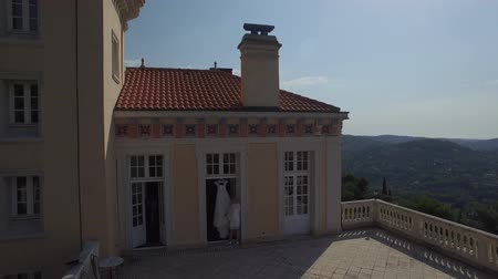 drone : Wedding dress at terrace. Bride touch wedding dress hanging on balcony of ancient castle in Europe France Grasse mountain area. Wedding agency planning day preparations. Fly over zoom out drone copter