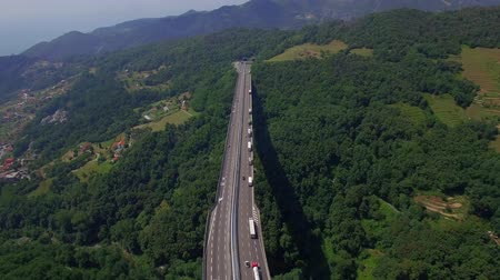 auto estrada : Highway bridge mountain viaduct road aerial 4k above top view. Cars lorry truck traffic Europe cargo freight logistics. Vehicles move on massive bridge overpass above green forest valley in Italy Alps