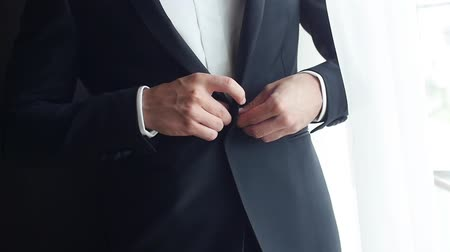 iyi giyimli : Stylish man in suit fastens buttons on jacket prepare to go out close up slow motion. No face man buttons jacket near window straightens collar pocket square. Establishment leadership fashion success Stok Video