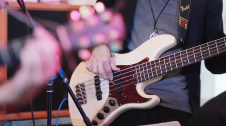 music band stage : Playing bass guitar rock music close up focus shift to electric guitar fret board with fingers pressing chords. Rock grunge boys band at stage performing at prom or concert gig club enthusiastically