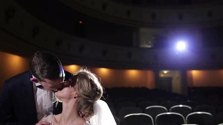 kino : Groom carefully kisses bride forehead calming her down in empty movie theatre close up slow motion. Couple tenderness care relationship love marriage concept. Romantic wedding scene in cinema hall