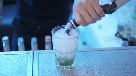 смешивание : Making alcohol cocktail pouring syrup into glass with ice close up slow motion. Bartender barman adds berries or fruit liqueur into beverage glass with mixed drink mojito at nightclub neon party light Стоковые видеозаписи