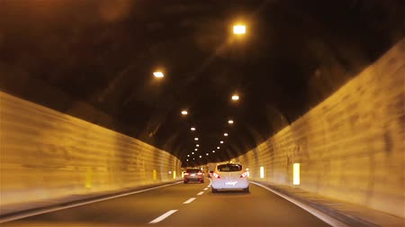 városi : Cars move in tunnel POV. Driving car in underground highway road tunnel under mountains. Riding cars hurry following lane. Sign and traffic rules in Europe vehicles transit infrastructure light in end
