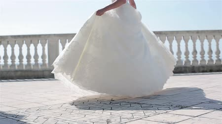 подвенечное платье : Woman in white dress spinning outdoors no face slow motion low angle. Bride in lace gown dance turning around on terrace balcony floor holding embroidered hem celebrating marriage wedding fashion show