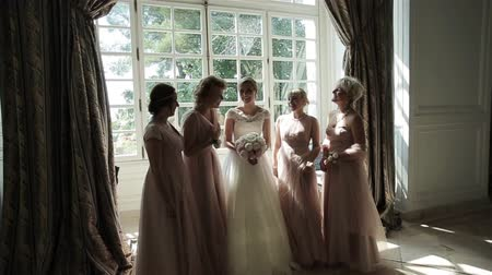 Bridesmaids laughing happy near bride slow motion. Beautiful girlfriends pose surrounding bride amusing and talking in sun light room. Bachelorette party emotional. Elegant wedding dress fashion style