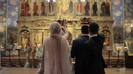 sacramental : Backs of maid of honor and best man standing behind bride and groom with crowns in hands above betrothed heads during wedding ceremony in front of icons altar in Orthodox church in Nice France closeup Stock Footage
