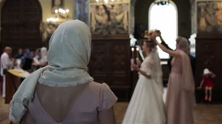sacramental : In church orthodox woman cross blessing herself with fingers and bow watching wedding ceremony view from back. Greek orthodox church rituals traditions customs. Religious people cult worship concept