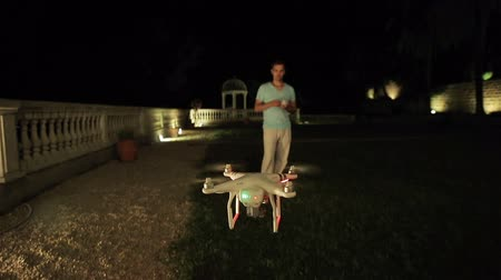 ahize : Drone quadcopter taking off from ground to night sky with operator controlling it side view. Man operates drone lighting up using remote controller. Guy pilots rc quadrocopter at black sky background Stok Video