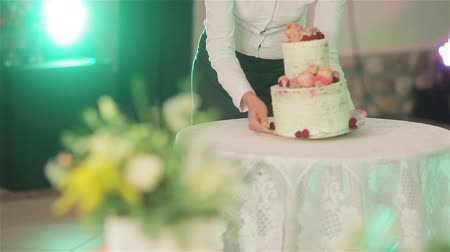 planejador : Waiter brings wedding cake and puts it on table under photo flash lights close up no face. Beautiful wedding cake decoration with natural roses blooms and berries. Banquet arrangement and catering