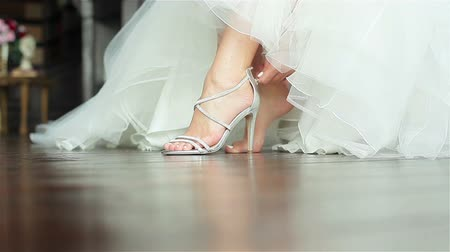 high heeled sandals : Woman puts on shoes hands close up shallow depth of field. Bride fastens zipper on luxurious high heeled sandals sitting in gorgeous white gown getting ready prepared for dancing at wedding ceremony Stock Footage