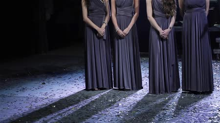 śpiew : Women in long dresses stand on stage with hands clasped and clap hands applauding unrecognizable no face legs close up. Slim bridesmaids in same elegant dress sing a song at wedding party reception