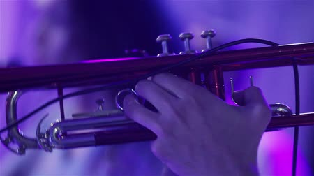 ska : Man playing trumpet blue light neon close up. Performing wind instrument at stage in night club at new years party holding trumpet with finders and blowing - woman singing background shallow dof