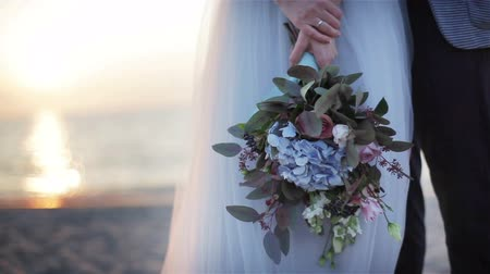 weddings : Unusual wedding bouquet close up outdoors. Woman hands hold bridal bouquet made from flowers and green leaves at sunset sea view background. Floral design decoration. Newlyweds posing at beach no face