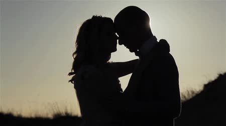 Couple embrace silhouetted at sunset sly background close up. Man and woman contrast shadow pose outdoors standing together under golden hour sun ray beams shining. Parting tenderness relationship Stock Footage