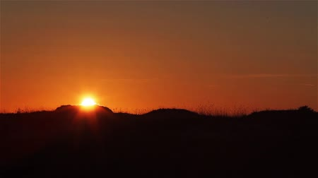 Sunset over hill dunes time lapse. Orange sky with fast setting sun over dunes with moving grass straws swaying in wind. Weather discovery channel style nomads life in steppes life and travel concept Stock Footage