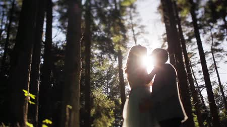 Man and woman in forest stand silhouetted together embracing and kissing backlit with shining evening sun tilt-shift close up. Wedding fashion outdoors in nature. Tenderness unity love dreams concept Stock Footage