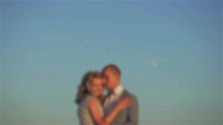 Man and woman blurred stand embracing at moon in blue sky background. Couple unfocused silhouetted kiss holding at lunar disk shining in clear sky space. Planning pregnancy moon phase cycles fertility