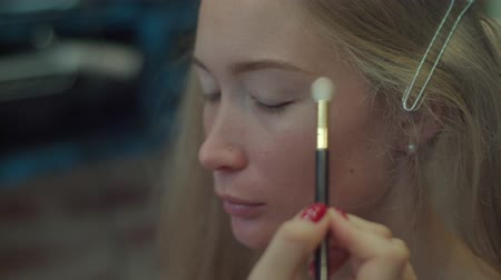 Applying eye shadows with makeup brush close-up 4k. Professional make-up artist visagiste puts light shadows on eyelid of blonde using holding brush with hand working. Nude day make up. Beauty industry