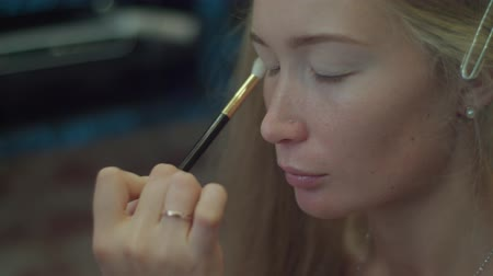 Apply eyeshadows with makeup brush close-up slow motion 4k. Professional make-up artist gently paints eyelid of Scandinavian blonde model with whites shadows using big brush. Nude day princess make up