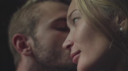 Couple having sweet moments stroking each other intimate scene head close up.  Lovers cuddle kissing. Young woman run fingers through boyfriends hair caressing his ear and man touch girlfriends nose Stock Footage